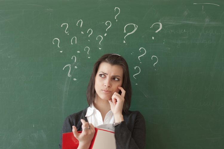 Image of student standing in front of a chalkboard with question marks written on the board